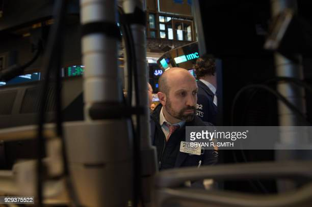 Traders work on the floor at the closing bell of the Dow Industrial Average at the New York Stock Exchange on March 8 2018 in New York US stocks...