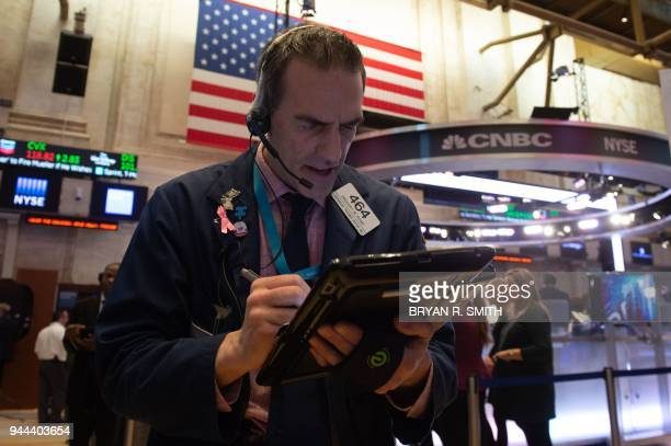 Traders work on the floor at the closing bell of the Dow Industrial Average at the New York Stock Exchange on April 10 2018 in New York / AFP PHOTO /...