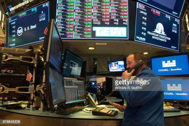 Traders work on the floor at the closing bell of the Dow Industrial Average at the New York Stock Exchange on June 19 2018 in New York Wall Street...