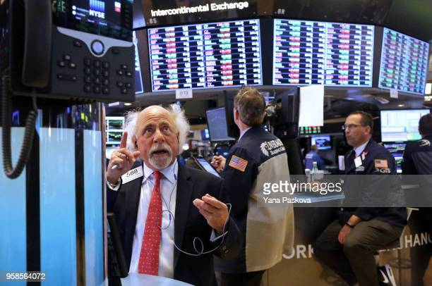 Traders work on the floor at the New York Stock Exchange after the ringing of the closing bell on May 14 2018 in New York City US stocks rose with...