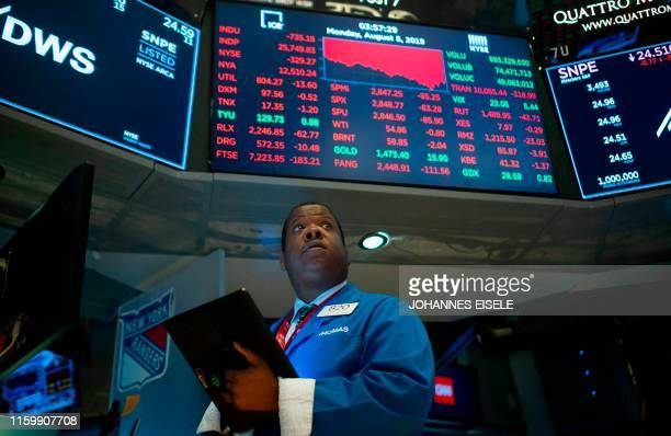 Traders work on the floor at the New York Stock Exchange on August 5 2019 at Wall Street in New York City Wall Street stocks plunged after a forceful...