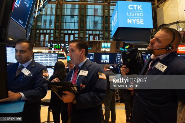 Traders work on the floor at the opening bell of the Dow Industrial Average at the New York Stock Exchange on September 28 2018 in New York
