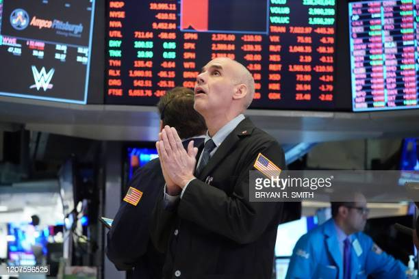 TOPSHOT Traders work on the floor at the opening bell of the Dow Industrial Average at the New York Stock Exchange on March 18 2020 in New York Wall...