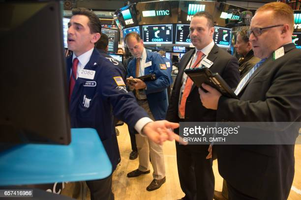 CORRECTION Traders work on the floor before the closing bell of the Dow Jones at the New York Stock Exchange March 24 2017 in New York / AFP PHOTO /...