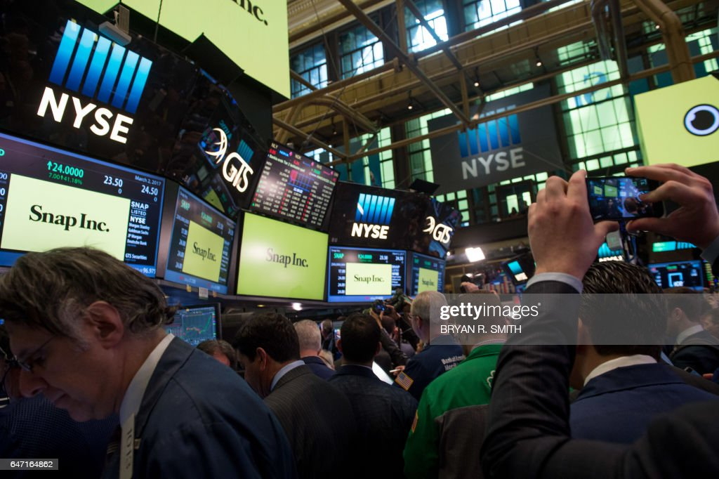 Traders work on the floor during the Snap Inc. IPO at the New York Stock Exchange, March 2, 2017, in New York. Snapchat surged in its debut trade Thursday, jumping more than 40 percent from the level set in the initial public offering Wednesday night. / AFP PHOTO / Bryan R. Smith