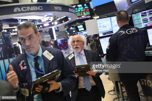 Traders work on the floor of the New York Stock Exchange after the Federal Reserve raised interest rates a move that investors expected on March 21...
