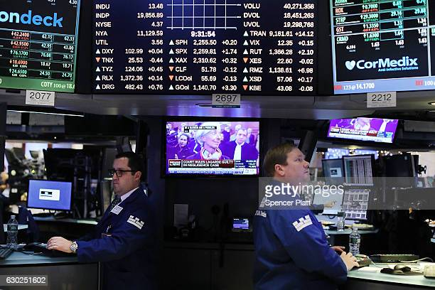 Traders work on the floor of the New York Stock Exchange as a picture of Christine Lagarde the managing director of the International Monetary Fund...