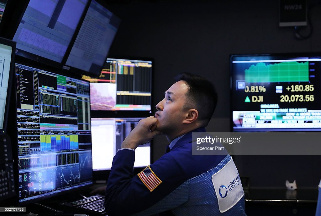 Traders work on the floor of the New York Stock Exchange (NYSE) as the Dow Jones industrial average closed above the 20,000 mark for the first time on January 25, 2017 in New York City. Solid earnings from major companies, including Boeing, led the morning rally.