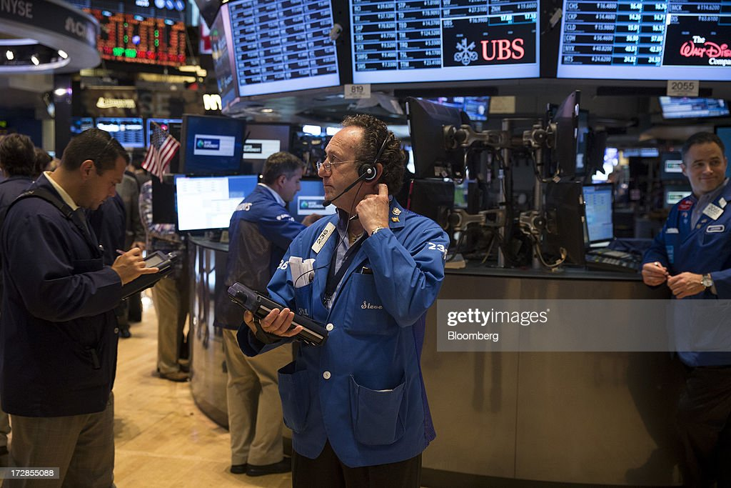 Traders work on the floor of the New York Stock Exchange (NYSE) in New York, U.S., on Friday, July 5, 2013. U.S. stocks fluctuated between gains and losses as faster-than-forecast jobs growth fueled bets the Federal Reserve will begin to reduce its bond buying. Photographer: Scott Eells/Bloomberg via Getty Images