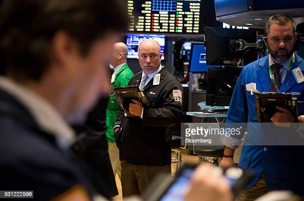 Traders work on the floor of the New York Stock Exchange in New York US on Friday May 13 2016 US stocks slipped amid lackluster results from large...