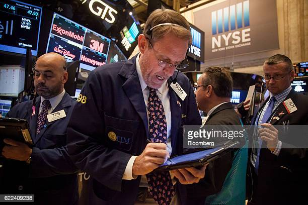 Traders work on the floor of the New York Stock Exchange in New York US on Friday Nov 11 2016 US stocks fluctuated in whipsaw trading with the Dow...