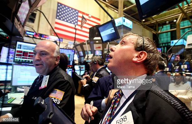 Traders work on the floor of the New York Stock Exchange moments before the closing bell October 30 2009 in New York City The Dow finished down 24985...