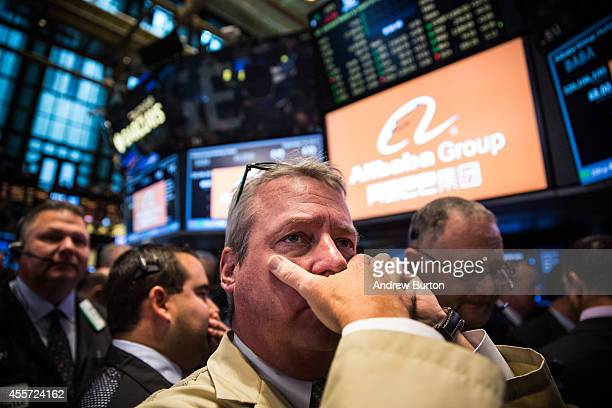 Traders work on the floor of the New York Stock Exchange while the price of Alibaba Group's initial price offering is decided on September 19, 2014...