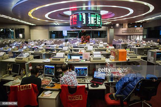 Traders work on the trading floor of the stock exchange in Hong Kong on February 3 2016 Hong Kong stocks plunged in the morning session on February 3...