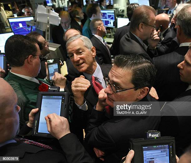 Traders work the floor as they wait for the first shares of VISA stock sold after the opening bell on the floor of the New York Stock Exchange March...
