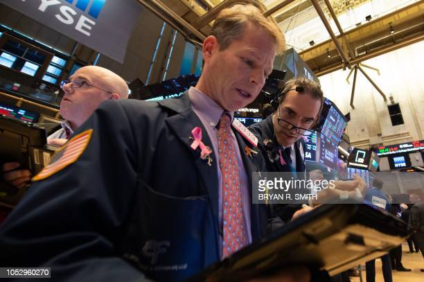 Traders work the floor at the closing bell of the Dow Industrial Average at the New York Stock Exchange on October 24 2018 in New York US stocks...