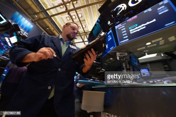 Traders work the floor of the New York Stock Exchange at the closing bell of the Dow Industrial Average October 24 2018 in New York US stocks...