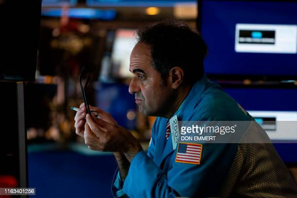 Traders work the floor of the New York Stock Exchange on August 23 2019 in New York Wall Street stocks tanked Friday after President Donald Trump...