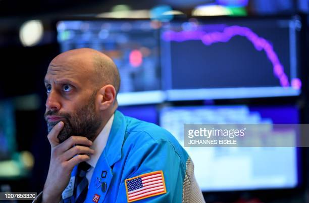 Traders works during the opening bell at the New York Stock Exchange on March 19 at Wall Street in New York City. - US stocks open mixed, Dow -0.4%,...