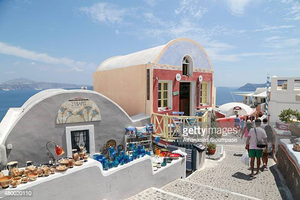 Tradisional house located atop the Oia caldera with wonderful views to the sea caldera and volcano and Visitors walk around the typifies the white...