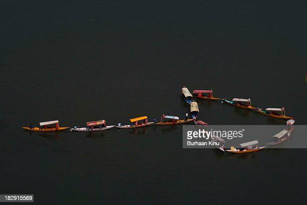Traditinoal Kashmiri boats arrange themselves in the shape of an arrow to signify movement towards a new direction in order to save the planet from...