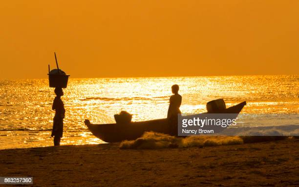 Traditional African Woman & Child &  Boat at Sunrise on Lake Malawi in Malawi.