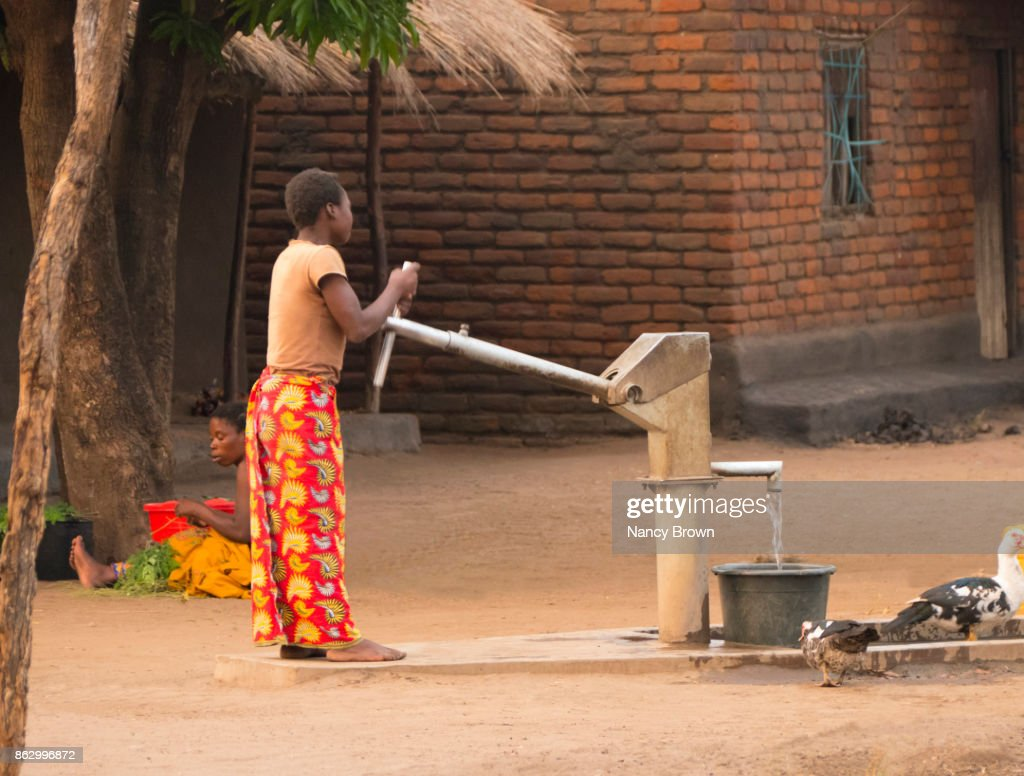 Traditional African Woman Pumping Water In Village Of Salima Malawi Stock Photo