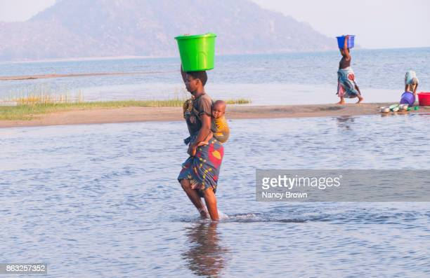 Traditional African Woman with Baby Walking by Lake Malawi in Malawi.