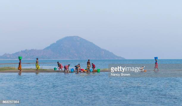 Traditional African Women Washing Dishes in Morning on Lake Malawi in Malawi.