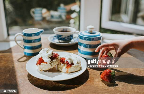 traditional afternoon tea of scones with jam and clotted cream - child grabs a strawberry - british culture stock pictures, royalty-free photos & images