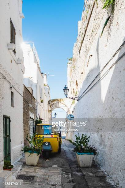 Traditional alley with three-wheeler in the city of Ostuni, Puglia, Italy