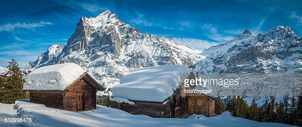 traditional alpine chalets in idyllic snowy winter mountains panorama switzerland - hut stock pictures, royalty-free photos & images