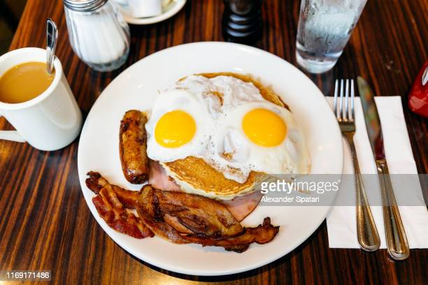 traditional american breakfast with pancakes, fried eggs, bacon, sausage and ham served in a diner - unhealthy living stock pictures, royalty-free photos & images
