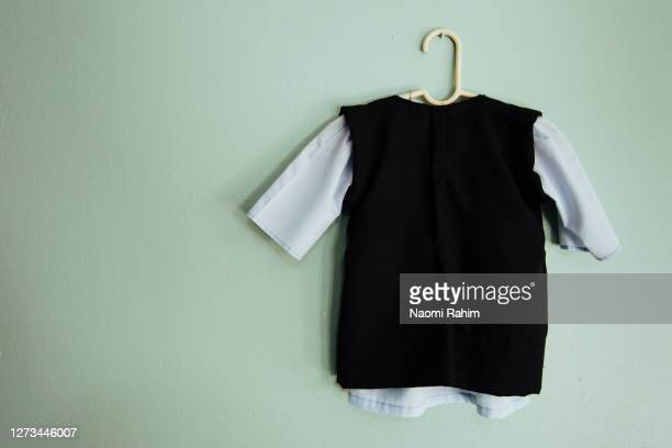 traditional amish baby clothing, hanging on a green wall - vest stockfoto's en -beelden