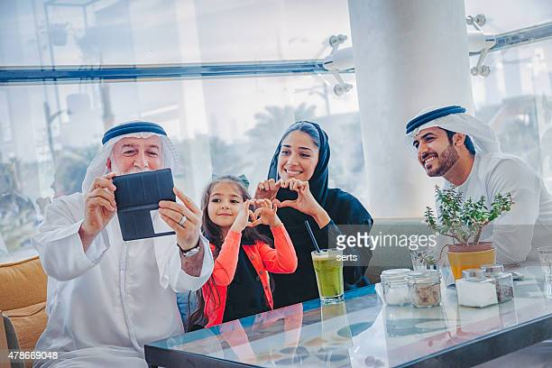 Traditional Arabian family taking selfie at cafe