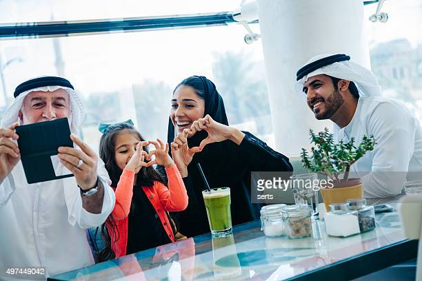 traditional arabian family taking selfie at cafe - symbol stock pictures, royalty-free photos & images