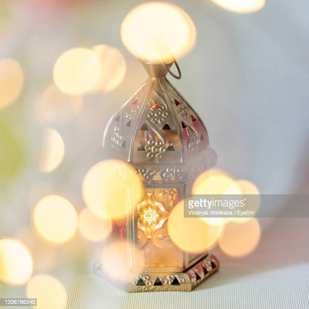 traditional arabic lantern lit up for celebrating holy month of ramadan with bokeh lights around it - eid mubarak stock pictures, royalty-free photos & images