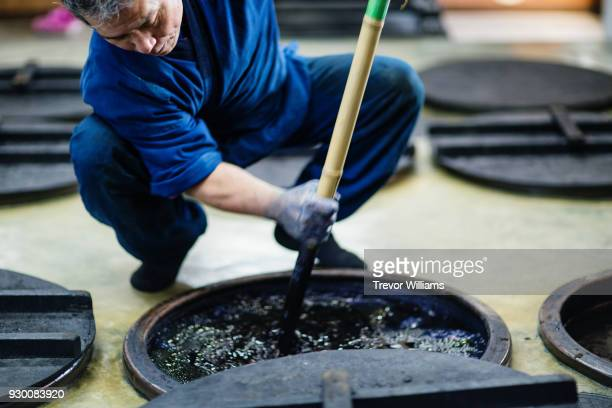 a traditional artisan mixing indigo dye in his studio - dye stock pictures, royalty-free photos & images