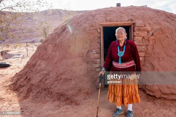traditional authentic navajo elderly woman posing in traditional clothing near a hogan in monument valley arizona - cherokee culture stock pictures, royalty-free photos & images
