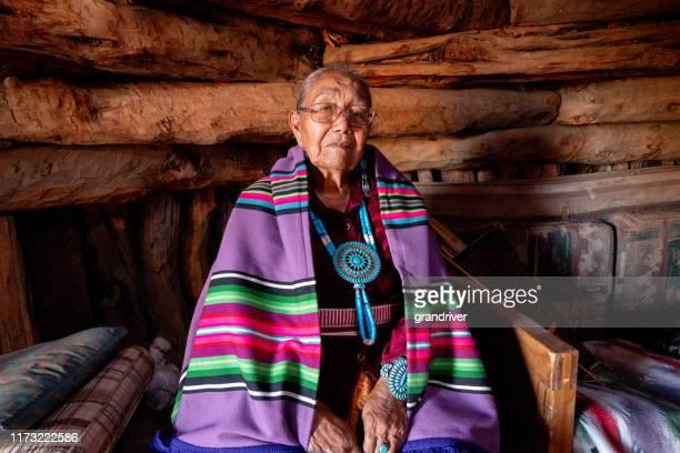 モニュメントバレーアリゾナ州のホーガンで伝統的な服を着てポーズをとる伝統的な本物のナバホ高齢女性 - ナバホ文化 ストックフォトと画像