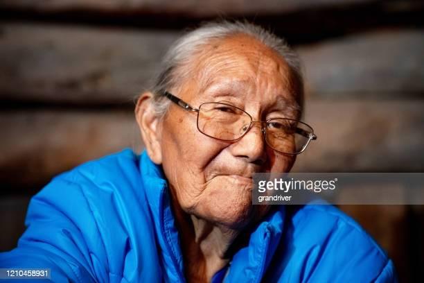 モニュメントバレーアリゾナ州のストック写真でホーガンで伝統的な服を着てポーズをとる伝統的な本物のナバホ高齢女性. - ネイティブアメリカン ストックフォトと画像