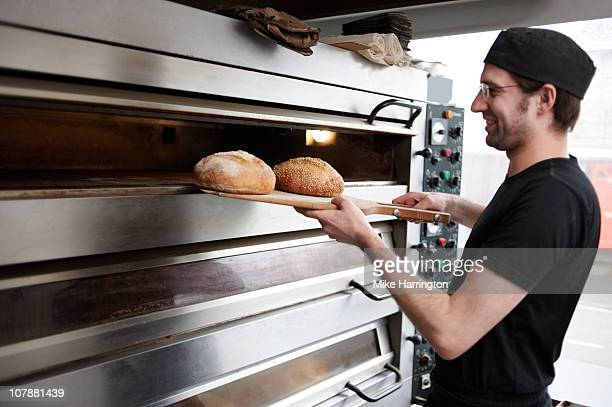 traditional baker removing bread from large oven - bakery stock pictures, royalty-free photos & images