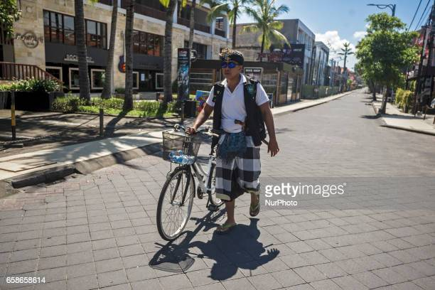 Traditional Balinese Guard known as Pecalang take a patrol at an empty road in Kuta Beach of Bali Island Indonesia during Hindu's Silence Day of...