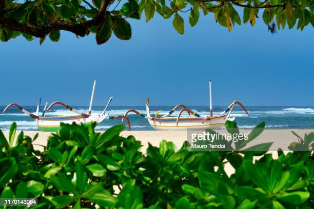 traditional balinese jukung fishing boats on nusa dua beach, bali - mauro tandoi stock photos and pictures