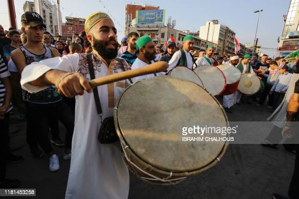 A traditional band performs in the streets of the northern Lebanese city of Tripoli to mark Prophet Mohammed's birthday in the midst of...