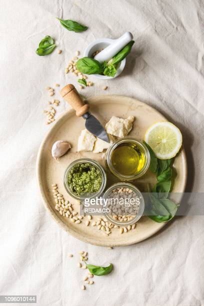 Traditional Basil pesto sauce in glass jar with ingredients above fresh basil, olive oil, parmesan cheese, garlic, pine nuts, lemon on ceramic plate...