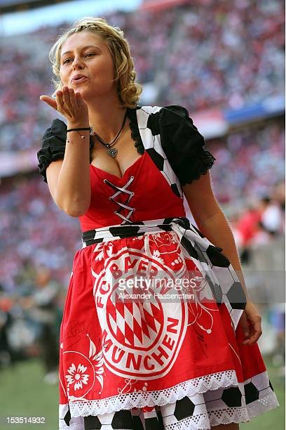 A traditional Bavarian dressed woman in a FC Bayern Muenchen Dirndl send kisses prior the Bundesliga match between FC Bayern Muenchen and TSG 1899...
