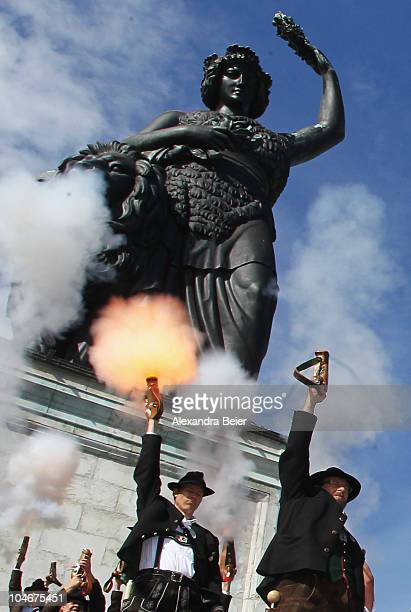 Traditional Bavarian riflemen and women shoot during a parade in front of the famouse scupture called 'Bavaria' during the Oktoberfest at...
