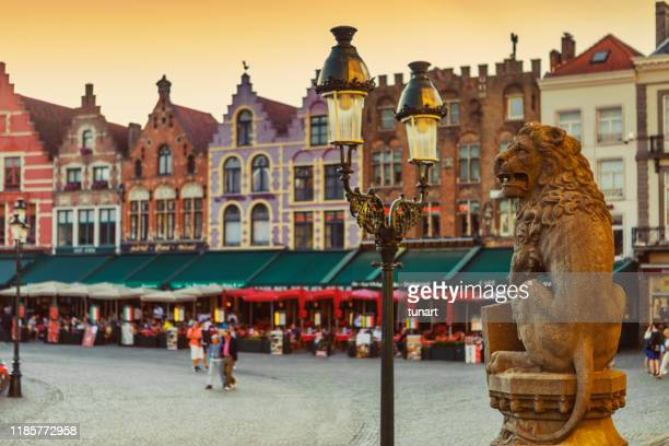 traditional belgian lion statue in front of city hall and colorful brick buildings in market square, bruges, belgium - bélgica imagens e fotografias de stock