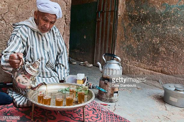 CONTENT] traditional Berber grandfather pouring tea in the Southern Atlas Mountains Morocco